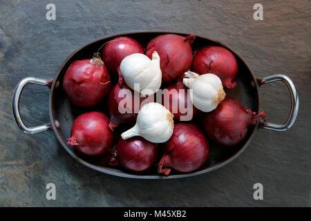 Oignons rouges et l'ail dans l'ancien bac de cuisson sur ardoise Banque D'Images