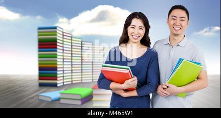Image composite de l'heureux couple holding books Banque D'Images