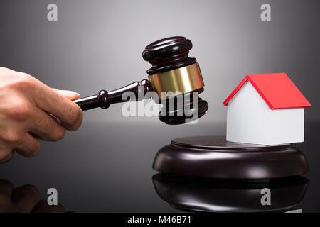 Close-up d'une main du juge Gavel frappant près de House Model Banque D'Images