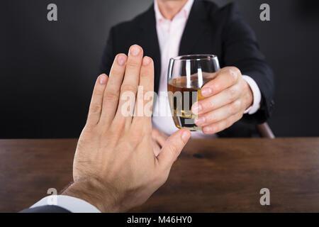 Businessman Hand le rejet d'un verre de Whisky offert par une femme d'affaires Banque D'Images