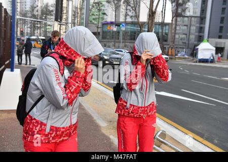 Gangneung, Corée du Sud. Feb 14, 2018. Des bénévoles luttant contre le vent fort à Gangneung, Corée du Sud, 14 février Banque D'Images