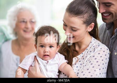 Smiling mother carrying baby avec le père Banque D'Images
