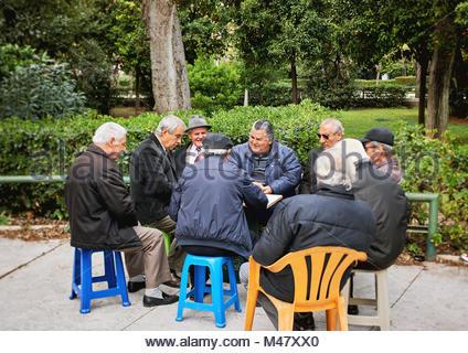 De vieux amis de cartes à jouer et rire dans le jardin National park Banque D'Images