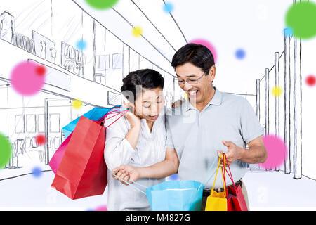 Image composite de l'older asian woman with shopping bags Banque D'Images