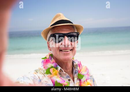 Happy senior man wearing flower garland sur la plage Banque D'Images