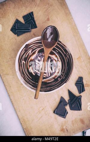 Le chocolat noir fondu et cuillère en bois sur un bol en céramique. Vintage filtre appliqué Banque D'Images