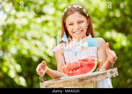 Smiling girl en tant que fille d'anniversaire est servant des pastèques Banque D'Images