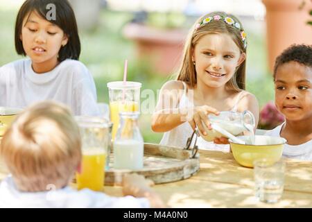 Groupe multiculturel d'enfants ayant le petit déjeuner ensemble au camp d'été Banque D'Images