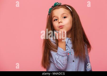 Portrait de l'adorable petite fille 5-6 ans avec de beaux longs cheveux auburn, soufflant de l'air kiss sur caméra Banque D'Images