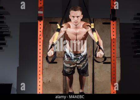 Formation TRX. Instructeur Crossfit au gym faire Excersise TRX. Banque D'Images