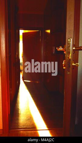 Un faisceau de lumière qui tombe sur le sol à travers la porte ouverte dans la chambre Banque D'Images