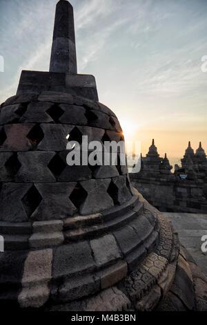 Rhombus troué stupa à Borobudur Temple bouddhiste au lever du soleil. Regency Magelang, Java, Indonésie. Banque D'Images