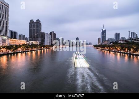 Bateau d'excursion, capturé avec blurred motion, navigue sur la rivière des Perles qui traverse le quartier du centre Banque D'Images