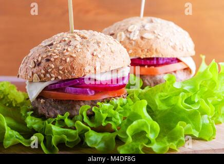 Cheeseburger avec oignons, tomates, salade et pain frais Banque D'Images