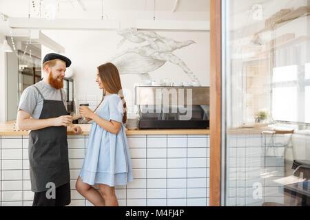 - Concept d'affaires Café smart jeune barman barbu aime parler et donner à emporter, tasse de café à la jolie client. Banque D'Images