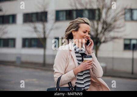 Businesswoman est au travail à pied dans la ville. Elle tient une tasse de café et parle au téléphone. Banque D'Images