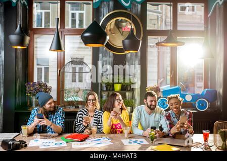 Amis assis avec téléphone dans le café Banque D'Images