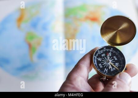 Hand holding compass en face de la carte du monde Banque D'Images
