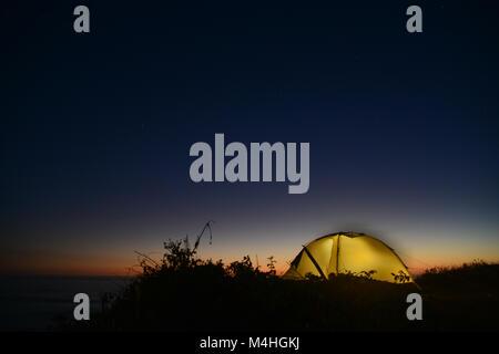 Silhouette d'un lumineux jaune tente à juste après la tombée de la nuit avec un ciel bleu foncé et la mer en arrière Banque D'Images