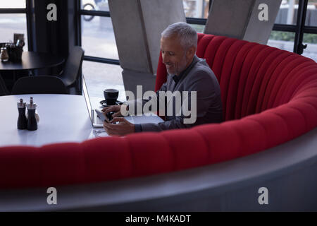 Businessman using mobile phone while working on laptop Banque D'Images