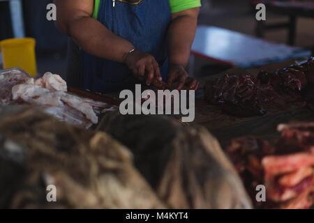 Couper la viande de boucherie au compteur dans une boucherie Banque D'Images