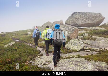 Les athlètes courent le long de la piste dans les montagnes en mauvais temps brumeux Banque D'Images