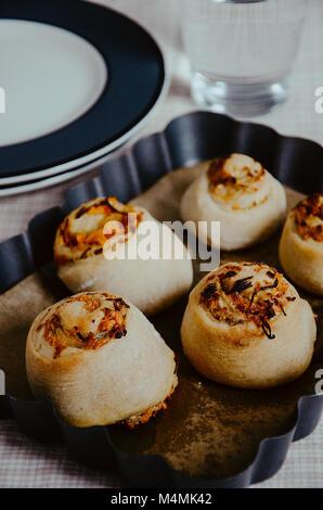 La levure pâtons ou brioches avec remplissage pizza de sauce tomate, fromage et jambon. Six pièces se situant dans Banque D'Images