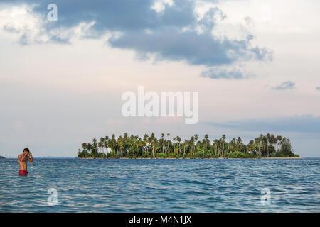 Snorkeler en rouge maillot de natation dans des eaux cristallines de l'eau de mer tropical turquoise sur Paradise Banque D'Images