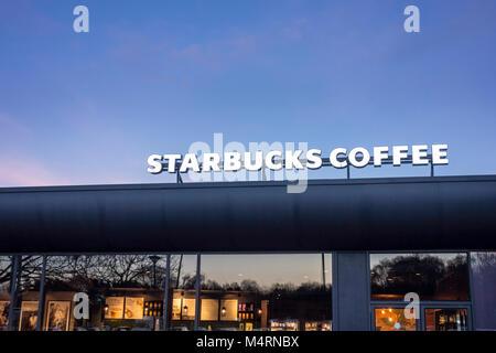 Café Starbucks lumineux affiche à l'extérieur d'une boutique dans la soirée, UK Banque D'Images