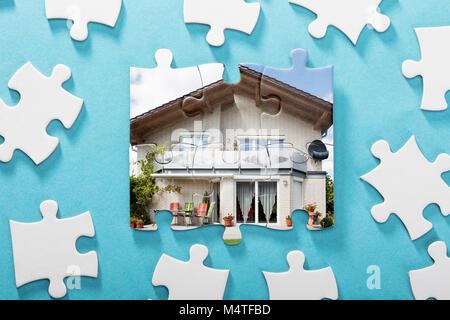 Close-up of Puzzle Maison incomplète sur fond bleu Banque D'Images