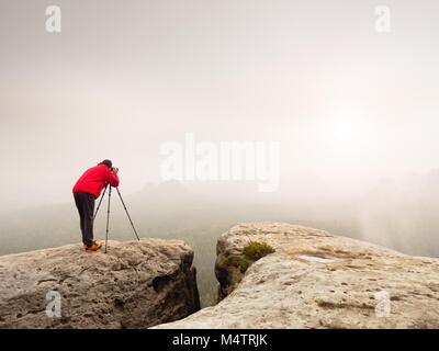 Photographe professionnel prise de vue. Artiste stay avec trépied sur sommet et prend des photos d'automne de la Banque D'Images