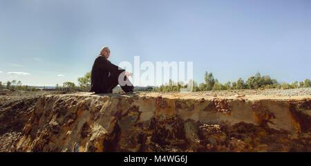 Un homme âgé assis sur le plancher Banque D'Images