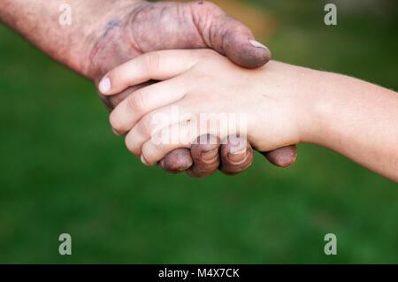 La main du père tient la main de l'enfant