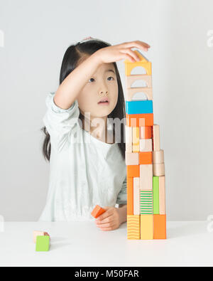 Little Asian girl playing de blocs en bois coloré Banque D'Images