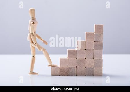 Vue latérale d'une figure en bois escalier d'escalade sur fond blanc Banque D'Images