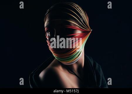 Femme avec du papier de couleur à la tête de canetage loin isolated on black