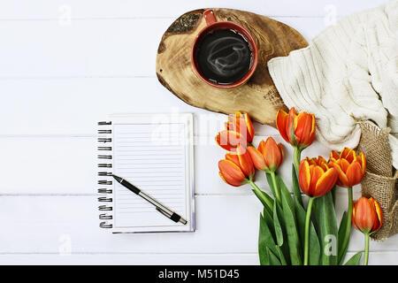 Les frais généraux ont tiré sur un bloc-notes avec stylo blanc, café et un bouquet de tulipes orange et jaune sur Banque D'Images