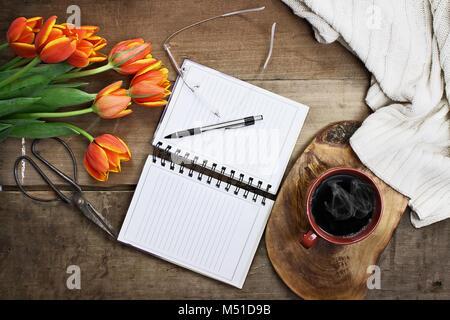 Passage tiré d'un bouquet d'un livre ouvert ou le jardin planner, verres, café, sissors et de fleurs sur une table Banque D'Images