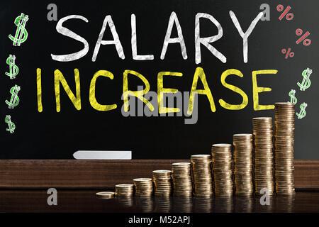 Augmentation de salaire mots sur tableau noir derrière les pièces empilées