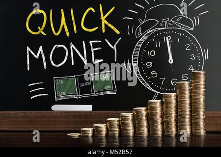 Mots d'argent rapide sur tableau noir derrière les pièces empilées
