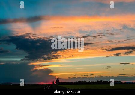 Une orange juteuse coucher du soleil avec une lueur pourpre un immense ciel bleu et nuages gris, sur un champ vert, Banque D'Images