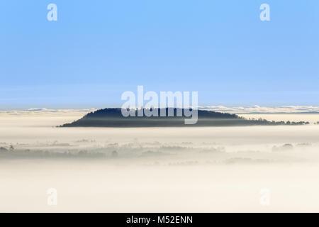 Matin brumeux avec vue sur une montagne au-dessus du brouillard