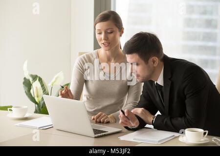 Jeune femme montrant des calculs pour patron Banque D'Images