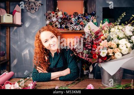 Fleuriste designer avec les cheveux rouges et les yeux verts qui travaillent à l'atelier du fleuriste Banque D'Images