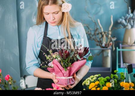 Displasing jeune fleuriste fleurs sur fond bleu
