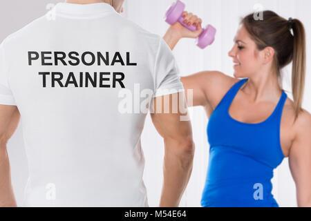 Jeune femme faisant de l'exercice avec haltère dans l'avant de l'entraîneur personnel Banque D'Images