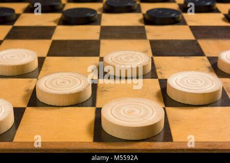 Pièces en bois noir et blanc dans la position de départ sur un damier