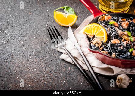 Dîner italien moderne, méditerranéenne, noir d'encre de seiche pâtes spaghetti aux fruits de mer, l'huile d'olive Banque D'Images