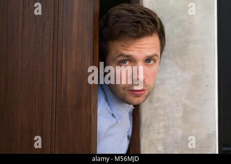 L'homme est à la recherche de sa télévision. Il ouvre la porte. Banque D'Images