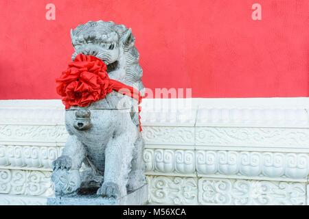 Statue en pierre traditionnelle d'un tuteur chinois lion (mâle), vêtu d'un gros noeud rouge autour du cou pour célébrer Banque D'Images
